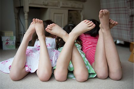 Girls lying on floor together with feet up Stock Photo - Premium Royalty-Free, Code: 614-07032046