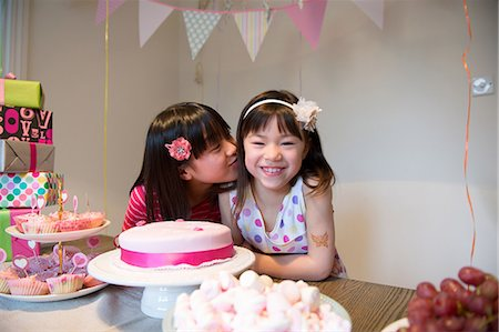 preteen kissing - Girl kissing friend at birthday party Stock Photo - Premium Royalty-Free, Code: 614-07032047