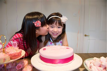 preteen kissing - Girl kissing friend at birthday party Stock Photo - Premium Royalty-Free, Code: 614-07032042