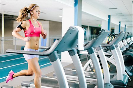 Young woman running on treadmill Stock Photo - Premium Royalty-Free, Code: 614-07032159