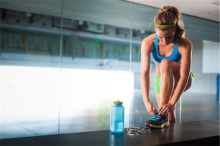 physical fitness - Young woman tying shoelace in gym Stock Photo - Premium Royalty-Free, Code: 614-07032168