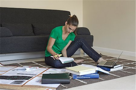 Mid adult woman sitting on floor studying Stock Photo - Premium Royalty-Free, Code: 614-07032180