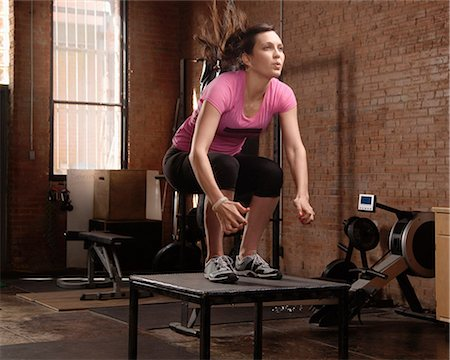 Young woman jumping on table in gym Stock Photo - Premium Royalty-Free, Code: 614-07032217