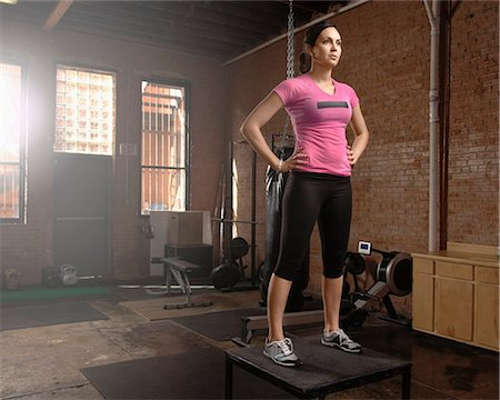 Young woman standing on table in gym Stock Photo - Premium Royalty-Free, Code: 614-07032218