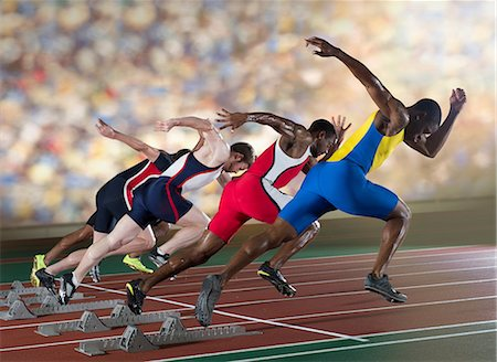 race track (people) - Four athletes starting a sprint race Stock Photo - Premium Royalty-Free, Code: 614-07145720
