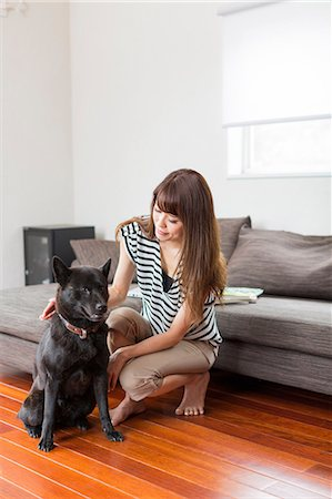 Woman with dog in living room Stock Photo - Premium Royalty-Free, Code: 614-07145869