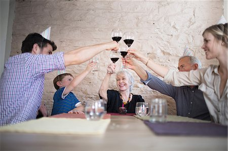 Family toasting with red wine at dinner table Stock Photo - Premium Royalty-Free, Code: 614-07145925