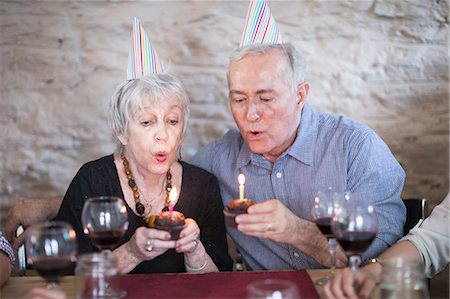 Senior couple blowing out birthday candles Stock Photo - Premium Royalty-Free, Code: 614-07145927