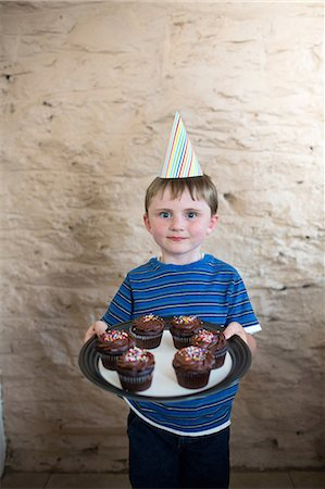 Portrait of boy wearing party hat holding cupcakes Stock Photo - Premium Royalty-Free, Code: 614-07145923