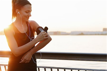 Young female jogger on riverside adjusting MP3 player Stock Photo - Premium Royalty-Free, Code: 614-07146055