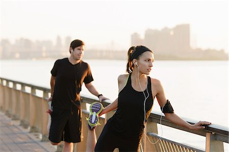 Jogging couple stretching on riverside early morning Stock Photo - Premium Royalty-Free, Code: 614-07146059