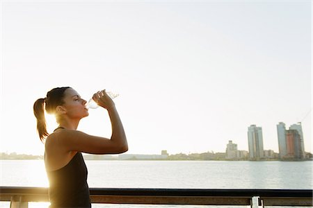 Young female jogger on riverside drinking water Stock Photo - Premium Royalty-Free, Code: 614-07146069