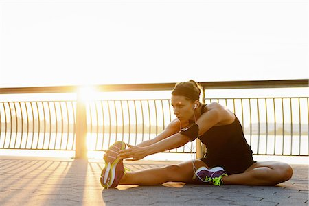 stretching (people exercising) - Young female jogger stretching at sunrise Stock Photo - Premium Royalty-Free, Code: 614-07146060