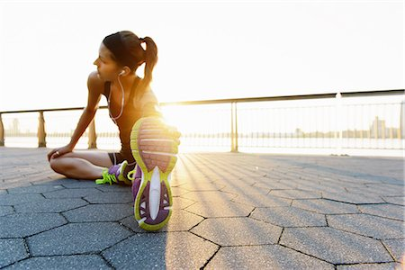 stretch - Young female jogger doing stretching exercise at sunrise Stock Photo - Premium Royalty-Free, Code: 614-07146061