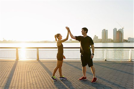 Jogging couple celebrating on riverside early morning Stock Photo - Premium Royalty-Free, Code: 614-07146062