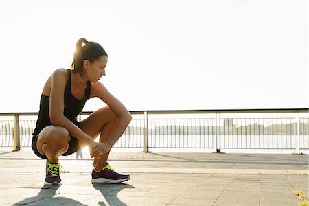 Young female jogger crouching and out of breath Stock Photo - Premium Royalty-Free, Code: 614-07146072