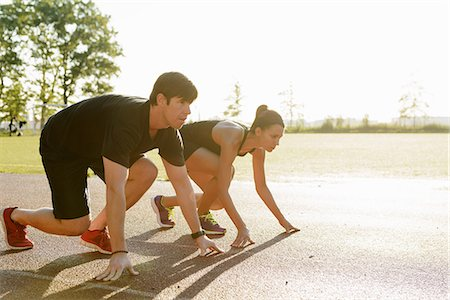 Couple preparing to race in city park early morning Stock Photo - Premium Royalty-Free, Code: 614-07146073