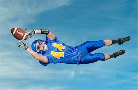 American footballer catching ball against blue sky Stock Photo - Premium Royalty-Free, Code: 614-07146106