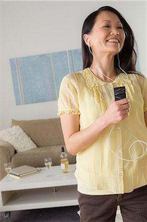 Mature dancing with mp3 player Stock Photo - Premium Royalty-Free, Code: 614-07146212