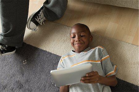 Boy lying on floor using digital tablet Stock Photo - Premium Royalty-Free, Code: 614-07146251