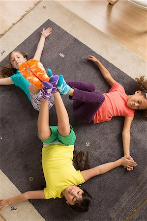 Three girls lying on floor with legs raised Stock Photo - Premium Royalty-Free, Code: 614-07146298