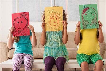 Three girls holding pictures over faces Stock Photo - Premium Royalty-Free, Code: 614-07146308