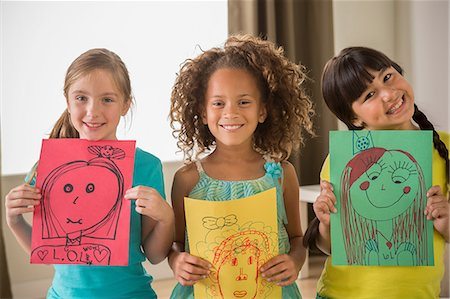 Three girls holding drawings of faces Stock Photo - Premium Royalty-Free, Code: 614-07146311