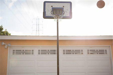 Basketball hoop and ball outside garage Stock Photo - Premium Royalty-Free, Code: 614-07146354