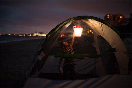 Boy in tent with lap at night, Huntington Beach, California, USA Stock Photo - Premium Royalty-Free, Code: 614-07146375