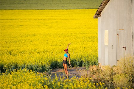 Young woman runner stretching in field of oil seed rape Stock Photo - Premium Royalty-Free, Code: 614-07146377