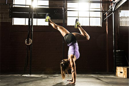 sports - Young woman in gym doing handstand Stock Photo - Premium Royalty-Free, Code: 614-07146415
