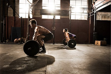 Two young adults working out with barbells in gym Stock Photo - Premium Royalty-Free, Code: 614-07146422