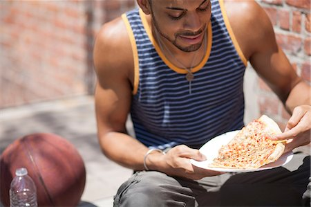 people eating at lunch - Basketball player with a slice of pizza Stock Photo - Premium Royalty-Free, Code: 614-07146481