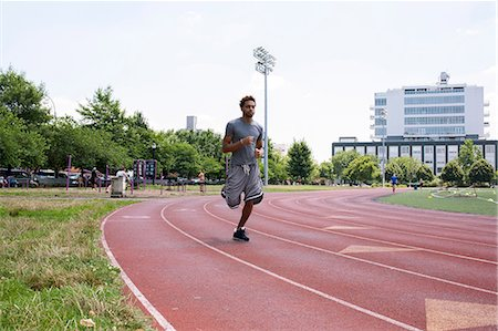 race track (people) - Young man running on outdoor track Stock Photo - Premium Royalty-Free, Code: 614-07146482