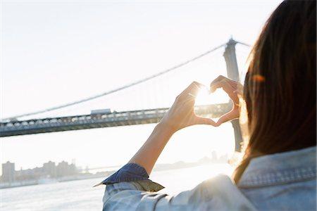 Woman's hands making heart shape, Manhattan Bridge, Brooklyn, USA Stock Photo - Premium Royalty-Free, Code: 614-07146625