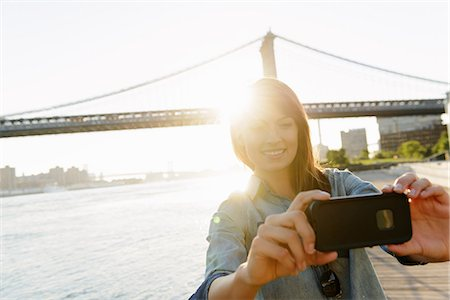 Young woman photographing herself with Manhattan Bridge, Brooklyn, USA Stock Photo - Premium Royalty-Free, Code: 614-07146622