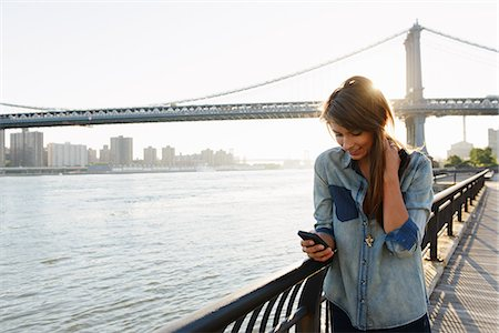 people and vacation - Young woman using cell phone, Manhattan Bridge, Brooklyn, USA Stock Photo - Premium Royalty-Free, Code: 614-07146623