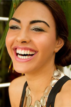 exotic outdoors - Portrait of young woman, smiling wearing circle necklace Stock Photo - Premium Royalty-Free, Code: 614-07194265