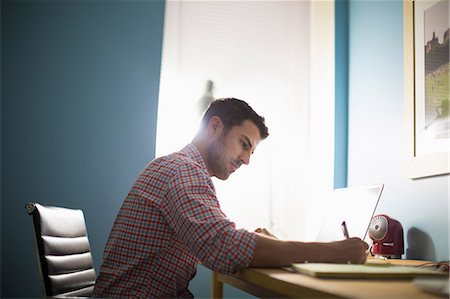 Man sitting at desk writing Stock Photo - Premium Royalty-Free, Code: 614-07194305