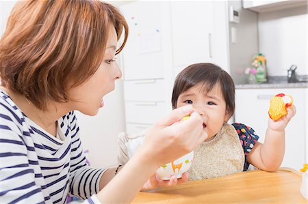 Mother feeding baby in kitchen Stock Photo - Premium Royalty-Free, Code: 614-07194394