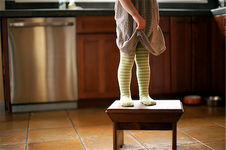 Cropped shot of toddler's legs standing on stool in kitchen Stock Photo - Premium Royalty-Free, Code: 614-07194445