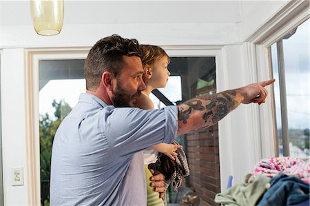 Father and daughter looking through window Stock Photo - Premium Royalty-Free, Code: 614-07194440