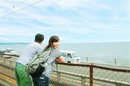 Young couple leaning against fence, looking out to sea Stock Photo - Premium Royalty-Free, Code: 614-07194474