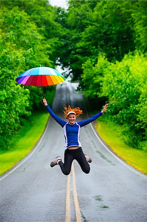 Teenage girl jumping with umbrella on road, Bainbridge Island, Washington, USA Stock Photo - Premium Royalty-Free, Code: 614-07194649