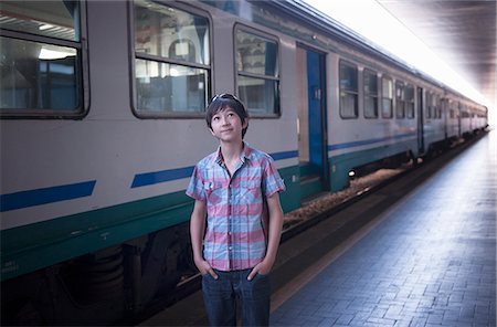 Boy by train with hands in pockets Stock Photo - Premium Royalty-Free, Code: 614-07194700