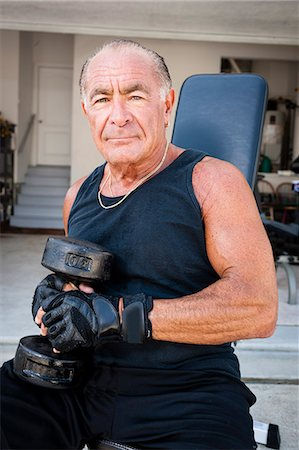 Portrait of muscular senior man holding dumb bells Stock Photo - Premium Royalty-Free, Code: 614-07194716