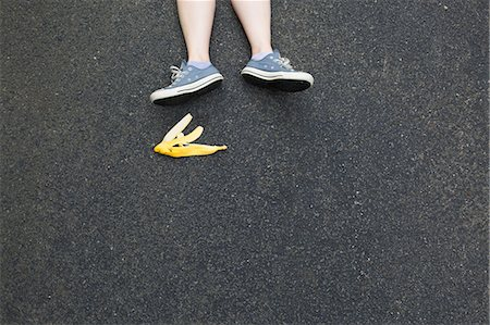 Pair of legs and banana skin on tarmac Stock Photo - Premium Royalty-Free, Code: 614-07194719
