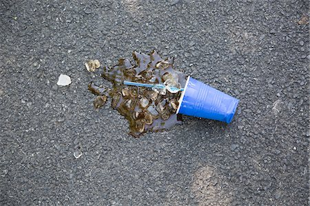 Spilled soft drink with plastic cup and ice cubes on tarmac Stock Photo - Premium Royalty-Free, Code: 614-07194720