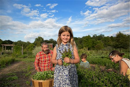 Portrait of girl holding bunch of leaves on family herb farm Stock Photo - Premium Royalty-Free, Code: 614-07194751