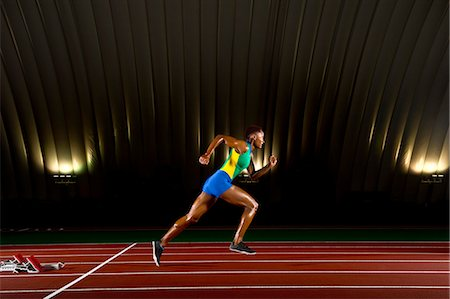 sprint - Young woman sprinting in stadium Stock Photo - Premium Royalty-Free, Code: 614-07234798